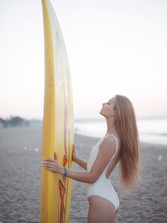 Girl with a longboard surf